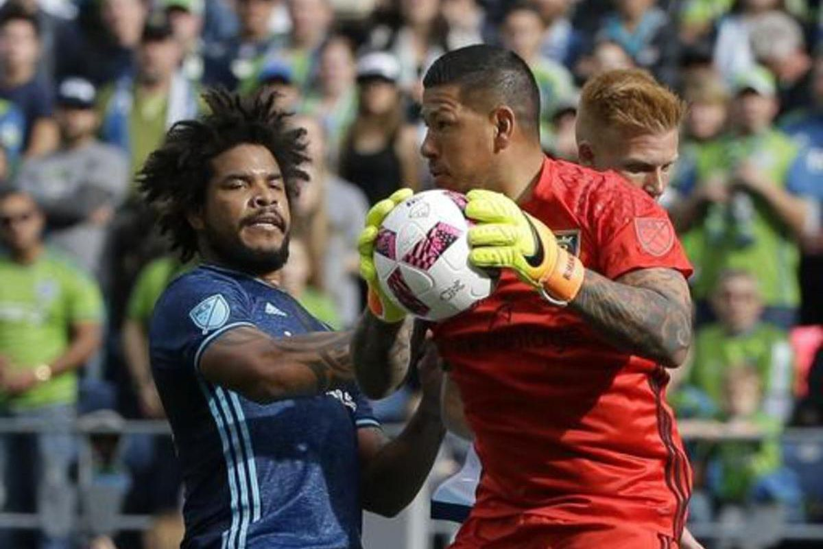 Real Salt Lake goalkeeper Nick Rimando, right, grabs a ball near Seattle Sounders defender Roman Torres, left, Sunday, Oct. 23, 2016, in the first half of an MLS soccer match in Seattle.
