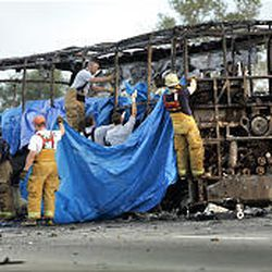 Firefighters work to cover and retrieve the bodies of nursing home residents who were killed when their bus caught fire on I-45.
