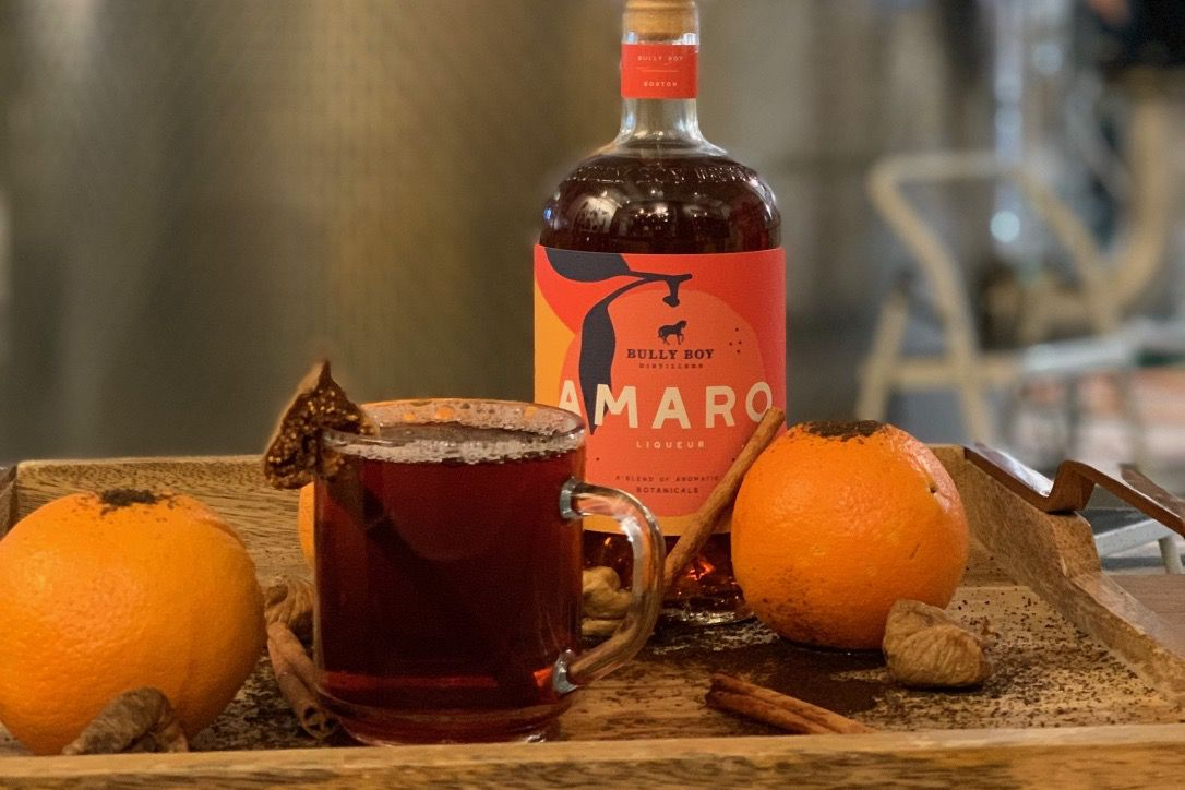 A dark tea-like hot cocktail sits in a glass next to a bottle of Bully Boy Distillers Amaro on a platter with cinnamon and oranges.