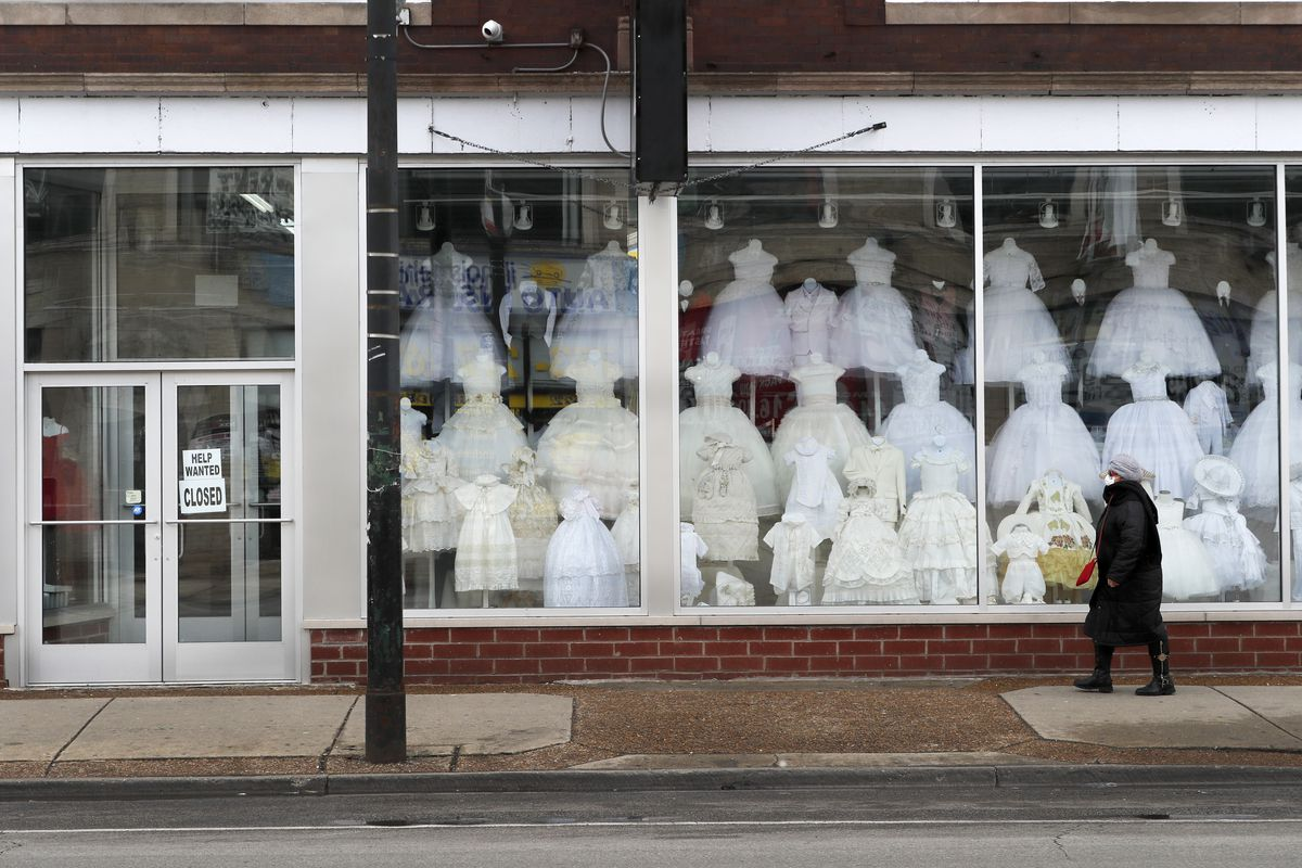 A woman wearing a protective mask walks past a closed children's clothing store in the Hispanic, Little Village in Chicago, Wednesday, April 15, 2020. The first U.S. economic indicators to capture the devastation brought on by the pandemic have begun to arrive, showing a plunge in retail sales exceeding what happened during the economic crisis a decade ago. (AP Photo/Charles Rex Arbogast) ORG XMIT: ILCA101