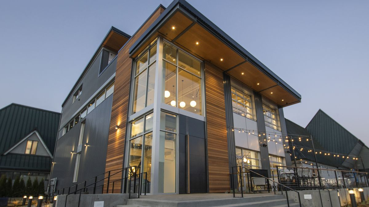 An exterior shot of the Hollywood Station building in Woodinville, with lights and wood trim, along with large steps leading up to the entrance next to an outdoor patio.