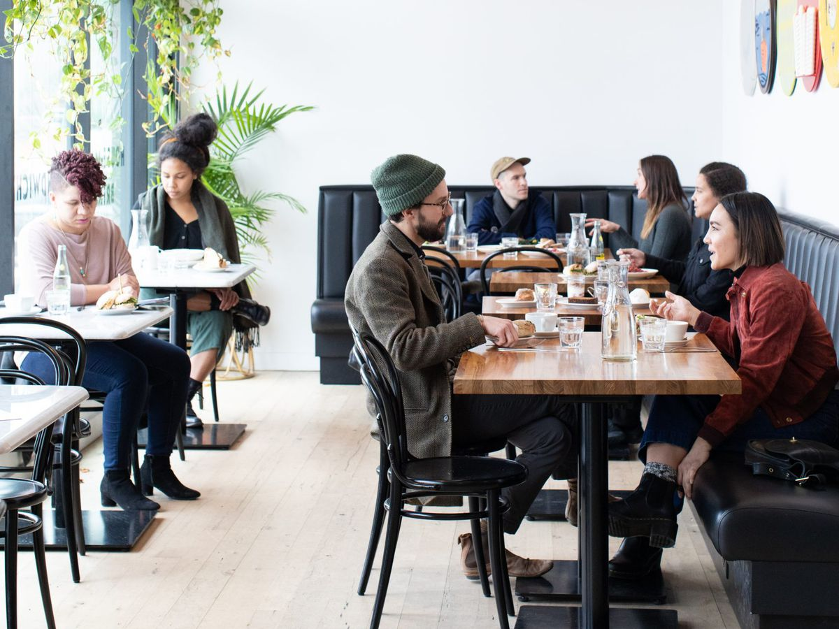 A stark white restaurant interior with patrons seated at various tables