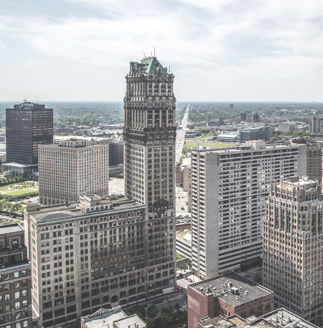 An aerial view of the Book Tower in Detroit. The facade is white with a green roof and multiple windows.