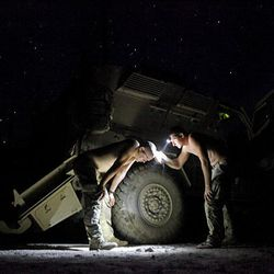 Sgt. Joshua Engbrecht, 28, of Riverside Calif., left, and Pfc. Jack Shortridge, 21, of Long Beach Calif., of the U.S. Army's 1st Platoon Apache Company, 2nd Battalion 87th Infantry Regiment, part of the 3rd Combat Brigade 10th Mountain Division based out of Fort Drum, N.Y.,  give each other haircuts under the stars at Combat Outpost Tangi in Afghanistan's Wardak Province Tuesday.