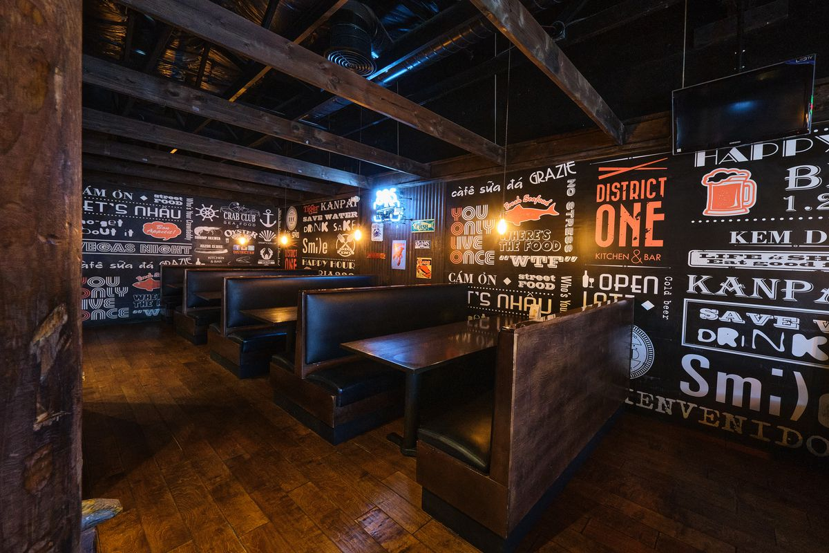 A restaurant booth area with chalkboard signs