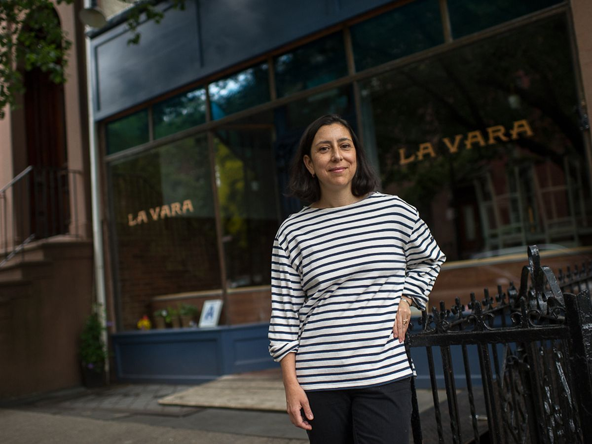 Chef Alex Raij stands in front of La Vara in a white-and-black-striped search with her hand on her hip