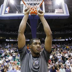 Utah Jazz forward Derrick Favors (15) hangs on the net prior to tipoff as the Utah Jazz and the Phoenix Suns play Tuesday, April 24, 2012 in Energy Solutions arena.