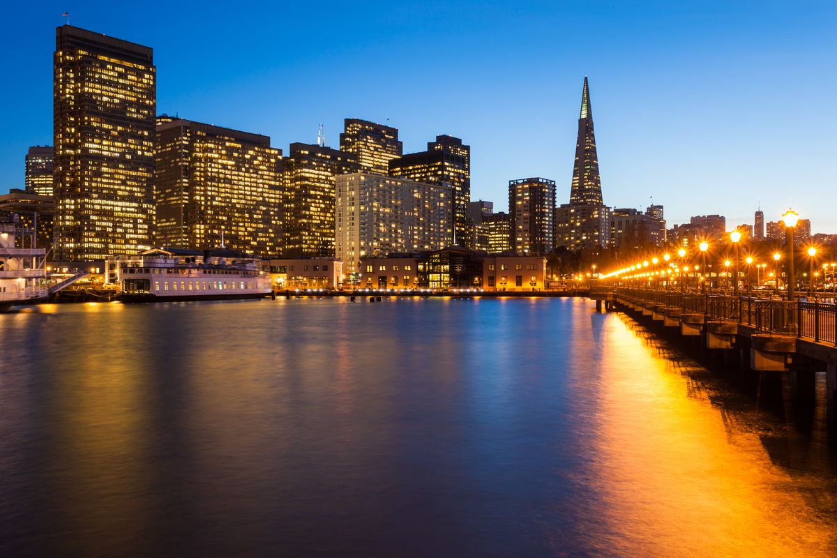 The San Francisco skyline at dusk with streetlamps reflected in the bay.