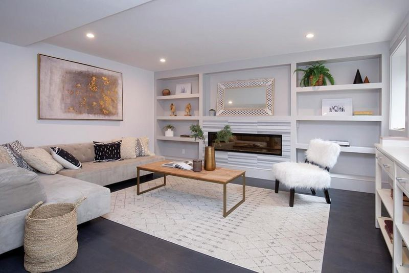 An airy living room with a chair and a sectional couch, and there are built-in shelves.