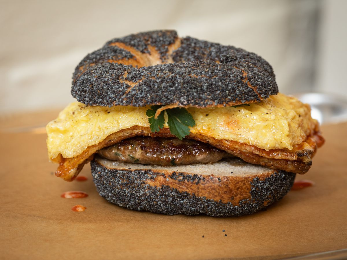 A bagel coated in sesame seeds is topped with egg, parsley, and a glistening sausage patty