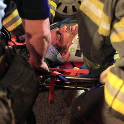 Emergency personnel remove an injured man from the site of a crane collapse where construction is going on for the 7 line subway extension Tuesday, April 3, 2012, in New York. Fire officials say the collapse at a Manhattan construction site has injured two people.