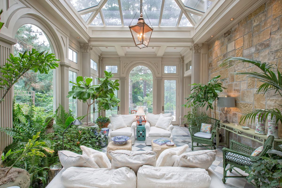 Traditional sunroom with white furniture.