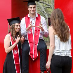"""Triplets Sophia Vitale and Ryan Vitale flash a """"U"""" while their sister Alex Vitale takes their portrait on the University of Utah's campus before a virtual commencement ceremony on Thursday, April 30, 2020."""