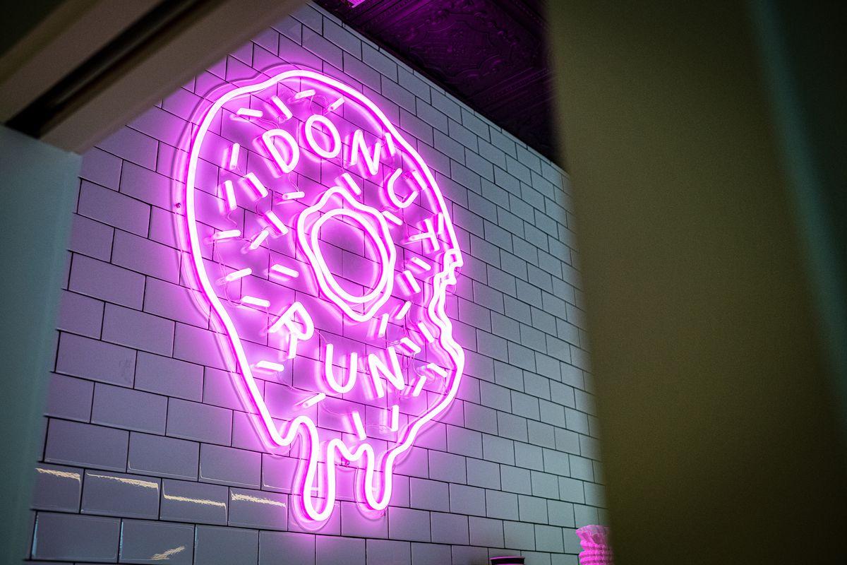 A pink neon doughnut hangs behind the counter at Donut Run