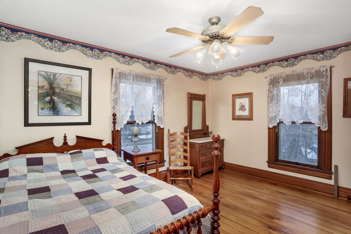 A large bed with a wood bed frame on hardwood floors. There's cream-colored walls and some wallpaper flower pattern near the crown.