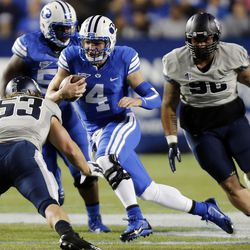 Taysom Hill (4) of the Brigham Young University Cougars runs the ball against USU during NCAA football in Provo, Friday, Oct. 3, 2014.
