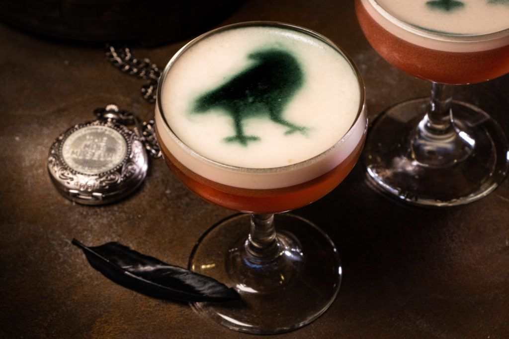 A cocktail with a crow in green on top in foam.