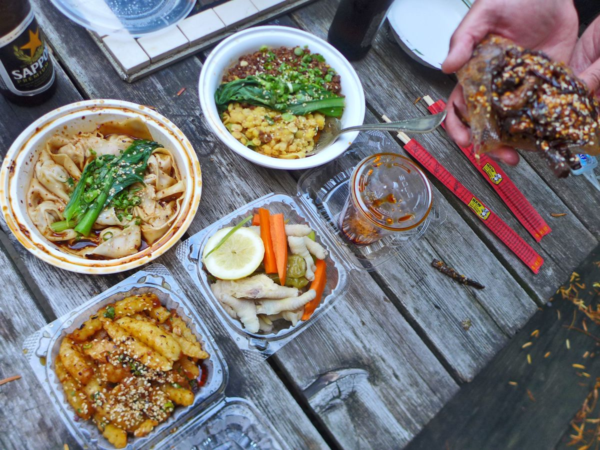 Several dishes in plastic containers placed on a wooden table