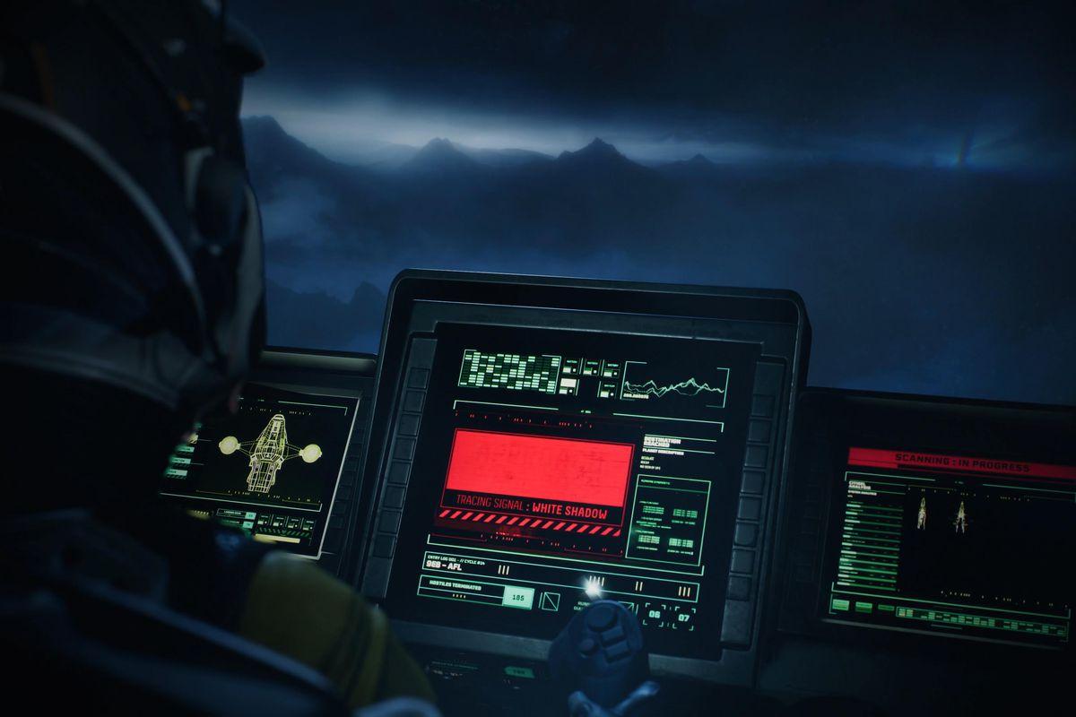 The main character of Returnal stares at a computer monitor
