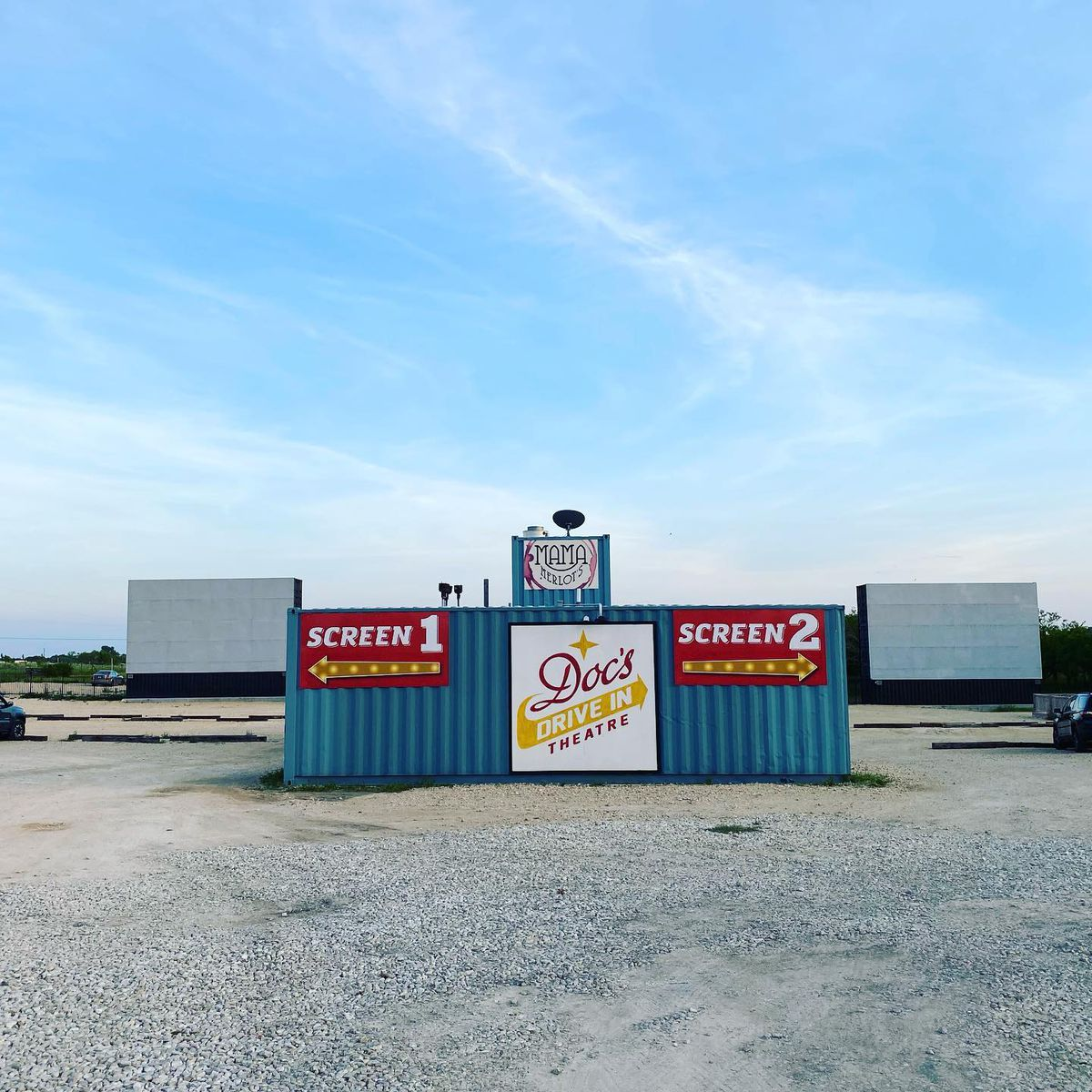 "A container unit with a white sign in the middle that reads ""Doc's Drive In Theatre"" and two red signs on the ends that read ""Screen 1"" and ""Screen 2"" with arrows pointing left and right respectively, and in the background are two blank movie screens, all outside"