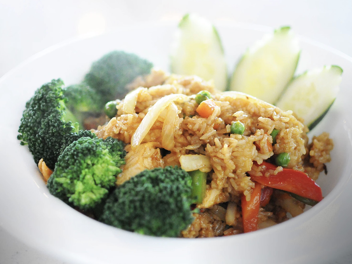 A white bowl filled with fried rice, broccoli, cucumber, and other vegetables.