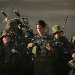 FILE - In this Dec.  20, 2006, file photo Israeli soldiers listen to their commander as they prepare for a march near Ein Yahav in southern Israel. A deadly shootout along Israel's border with Egypt on Friday, Sept. 21, 2012 has shone a spotlight on Israel's only mixed female and male combat unit, granting some recognition to a group that has faced much skepticism and often been the butt of jokes since its inception. Friday's attack was a major test for the Caracal Battalion, which is used to more tame operations, and the soldiers' participation was credited with helping to slay the three gunmen.