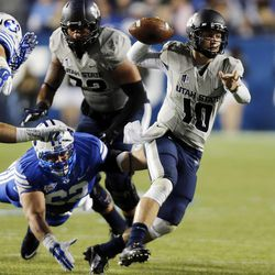 Darell Garretson (10) of the Utah State Aggies scrambles during NCAA football in Provo, Friday, Oct. 3, 2014. Diving is Logan Taele (62) of the Brigham Young University Cougars.
