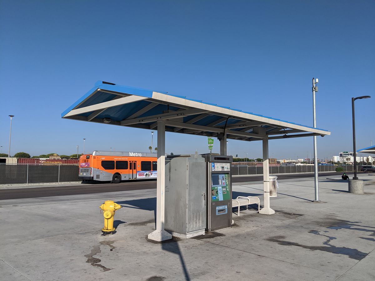 A bus plaza with a bench and ticket vending machine sits empty under a bright blue sky while a bright orange city bus idles in the background.