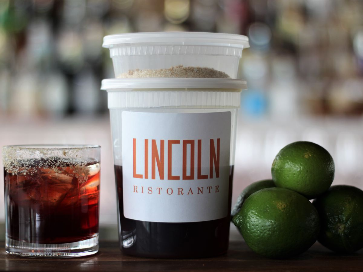 """A plastic to-go container with the label """"Lincoln Ristorante"""" in red lettering sits between a dark-colored cocktail and a stack of three limes"""