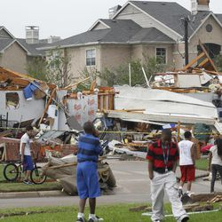 Neighbors view what remains of a home in Arlington, Texas, Tuesday April 3, 2012. Tornadoes tore through the Dallas area Tuesday, peeling roofs off homes, tossing big-rig trucks into the air and leaving flattened tractor trailers strewn along highways and parking lots.