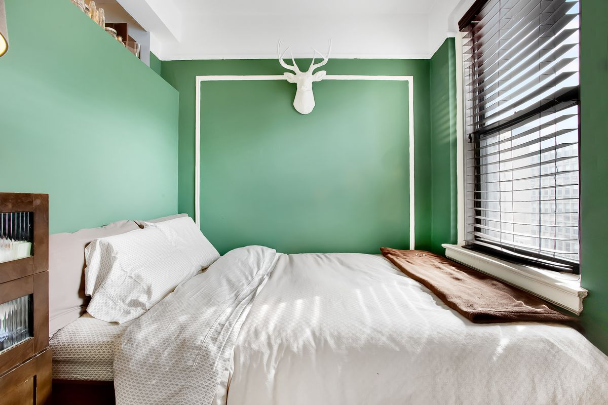 A bedroom with bright green walls, a large bed, a window, and a white deer bust.