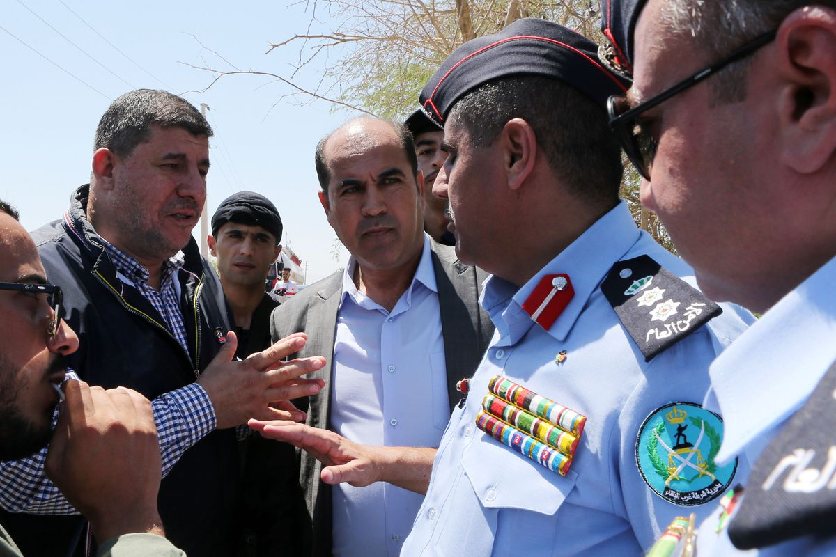 Yahya Soud is surrounded by a group of men and talks with a man in a police uniform.