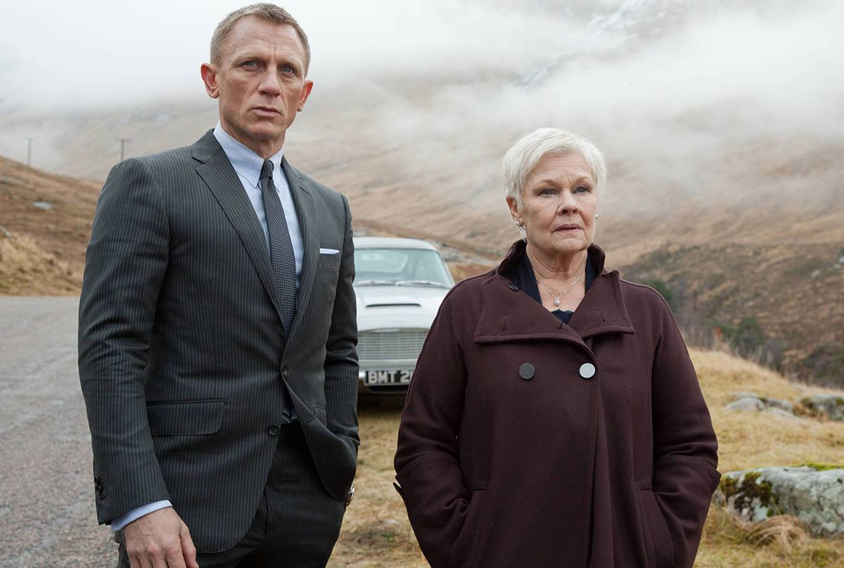 Bond and M stand in front of a fancy car in misty Scotland in Skyfall