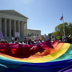 Demonstrators stand in front of a rainbow flag of the Supreme Court in Washington, Tuesday, April 28, 2015. The Supreme Court heard historic arguments in cases that could make same-sex marriage the law of the land.