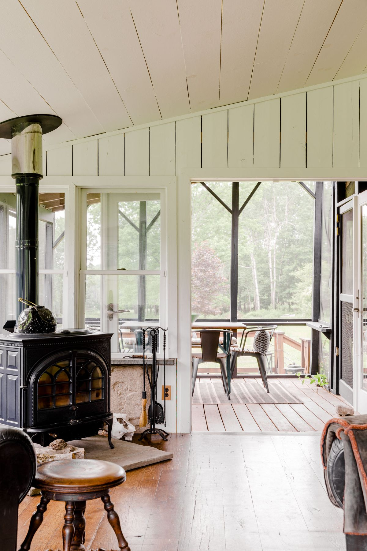 A living area with a woodstove overlooks an enclosed deck with a wall of windows overlooking a tree-lined yard