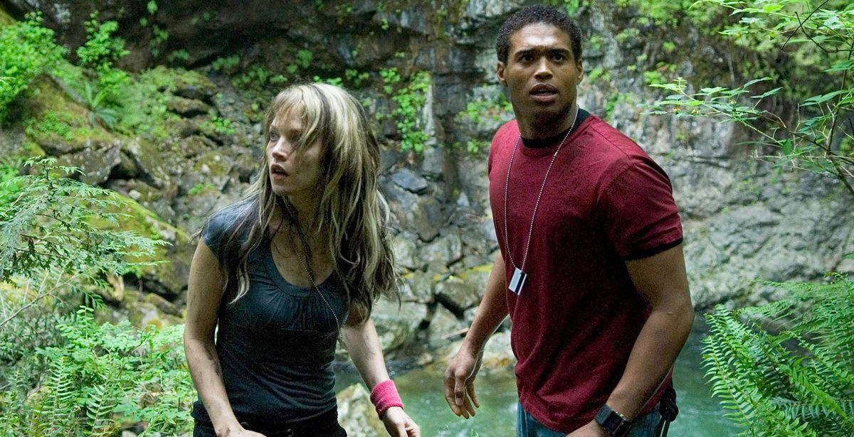 A thin white woman with black-and-white hair and a tall black muscular man stand together in the woods, both looking nervously in different directions.