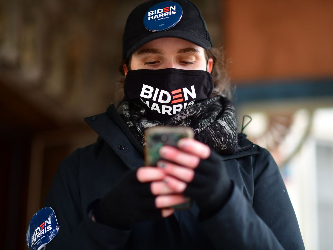 A person wearing a Biden-Harris campaign face mask looks at their phone.