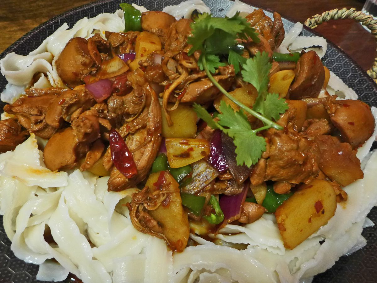 A spicy chicken melange on a bed of broad ruffled noodles.