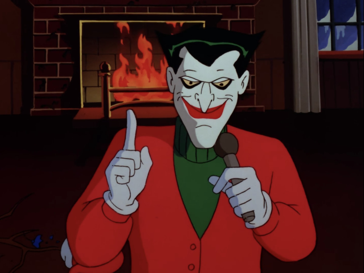 """The Joker, dressed for Christmas, addresses the audience in front of a blazing hearth, in """"Christmas with the Joker,"""" from Batman: The Animated Series."""