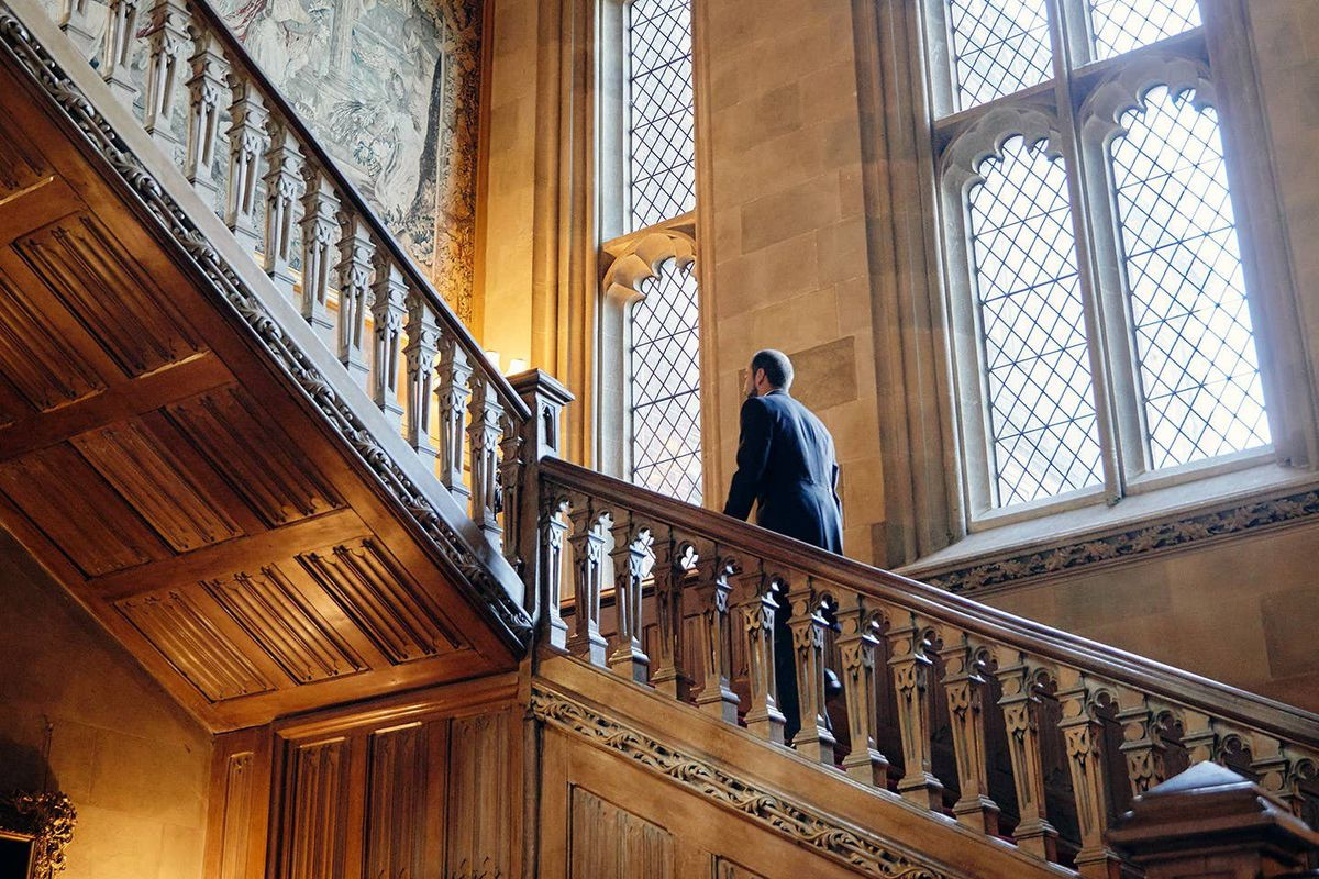 A man walks up a staircase next to large windows.