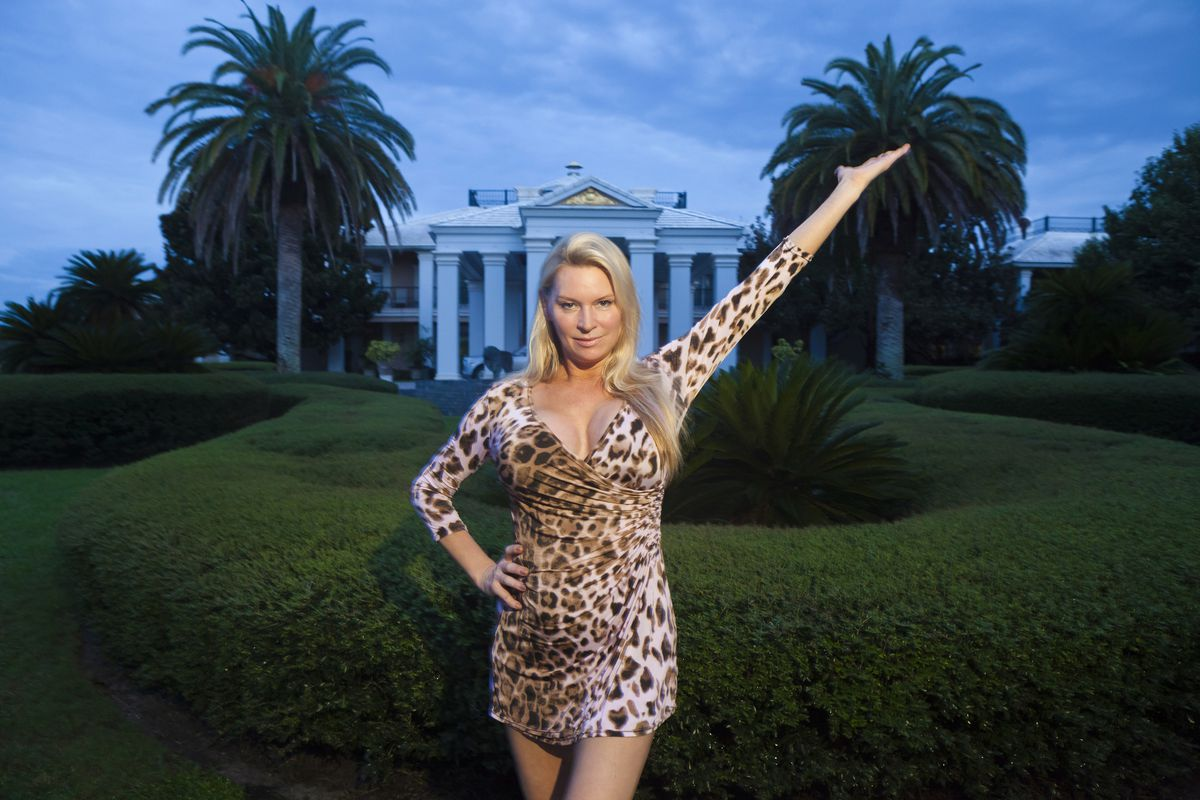 Jackie, wearing in a leopard-print dress, strikes a pose in front of her giant house.