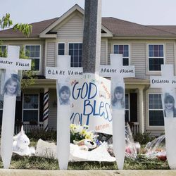 FILE - In this June 15, 2007 file photo, a makeshift memorial to Kimberly Vaughn, and her three children Abigayle, 12, Cassandra, 11, and Blake, 8, is seen outside their home in Oswego, Ill. Closing statements are scheduled  to begin Thursday, Sept. 20, 2012, in Joliet, Ill., in the murder trial for Christopher Vaughn, accused of shooting dead his wife Kimberly and three kids as the family drove to a waterpark in 2007.