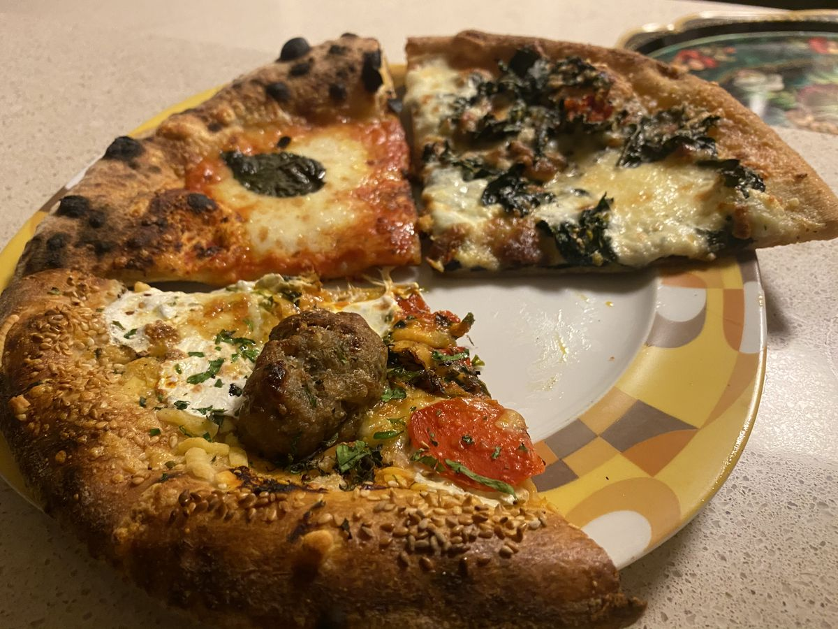 A meatball pizza with roasted red peppers from Peasant sits next to a margherita slice from the same venue, which in turn sits next to a kale slice from Smillie Pizza