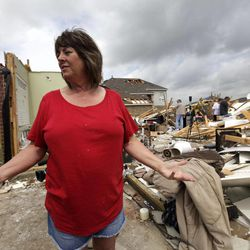 Sherry Enochs, stands in what is left of her home as she recounts the tornado that struck her home Wednesday, April 4, 2012, in Forney, Texas. Enochs was babysitting three children all under the age of 3, when the tornado struck. All survived the storm with minor bumps and bruises.