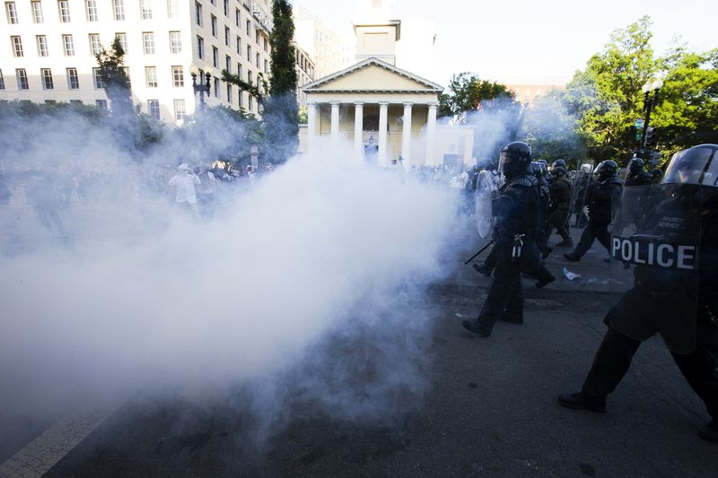 Buildings and protesters are obscured by a dense cloud of white gas — the only clear area, to the right of the photo, shows police in riot gear marching forward.