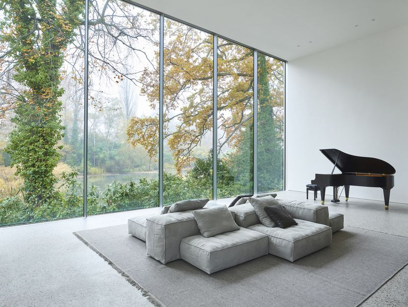 A high-ceilinged room contains a wall of windows, a gray sofa set, and a grand piano.