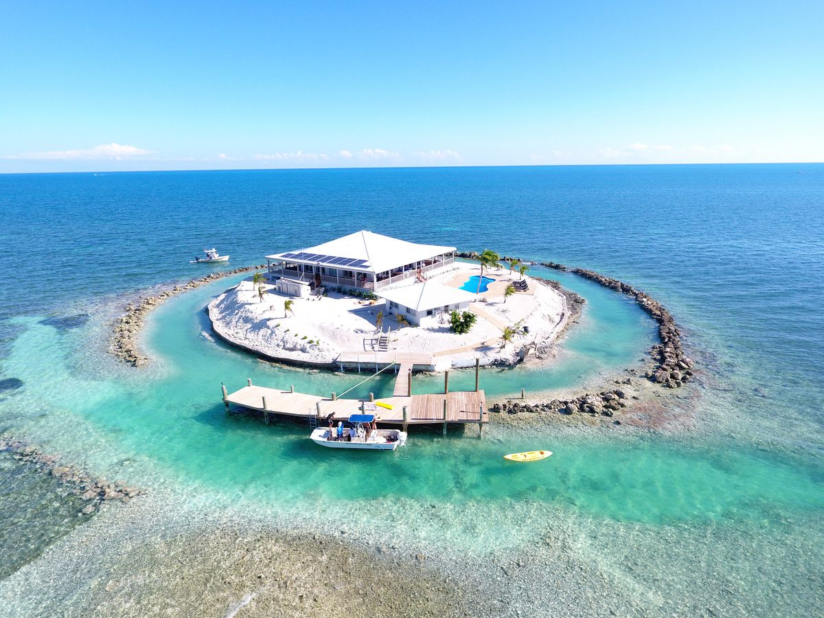 An island house is encircled by a reef with water all around. A boat is parked at the dock, and the aerial view shows a swimming pool.