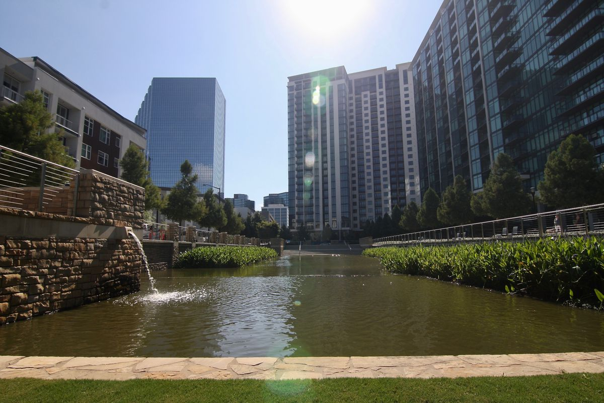 A pond with greenery at the edges and classy towers at the rim.