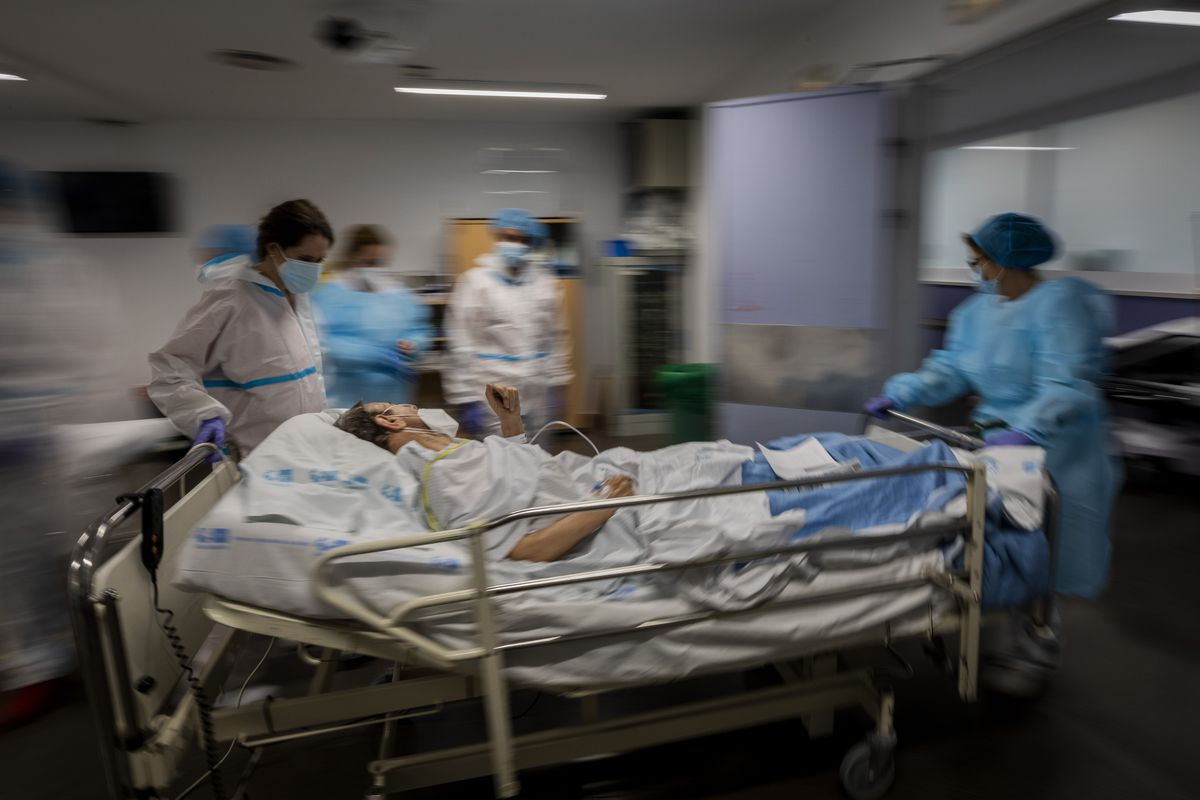 """In this Feb. 17, 2021, file photo, a COVID-19 patient is transferred to the """"red zone,"""" an area reserved for treating those suffering from COVID-19, in the Severo Ochoa Hospital in Leganes on the outskirts of Madrid, Spain."""