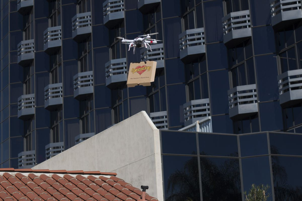 A drone carrying a box of pizza.